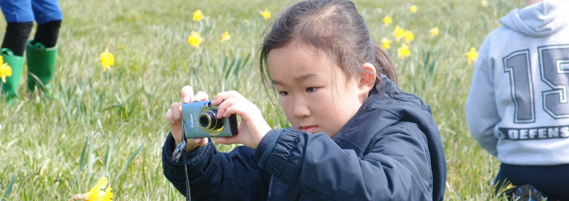A young girl taking a photo