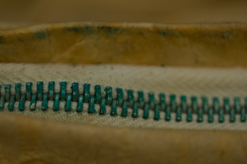 Copper in the zipper alloy reacts with the fatty acids in the buckskin, producing bright green verdigris, consuming the metal and staining the skin.